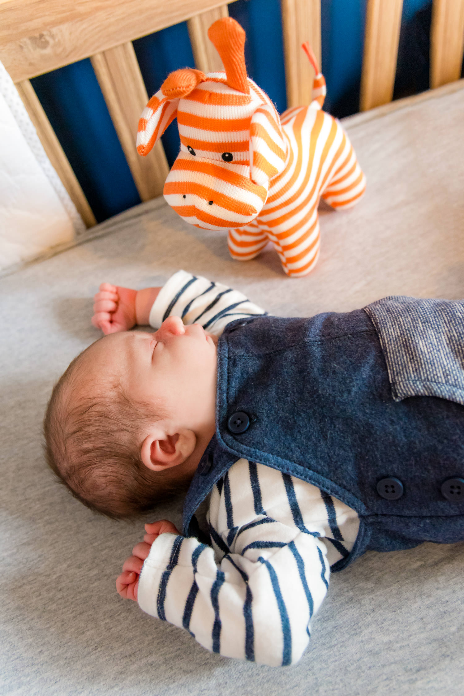 newborn baby asleep in cot with orange stripy toy during maternity shoot