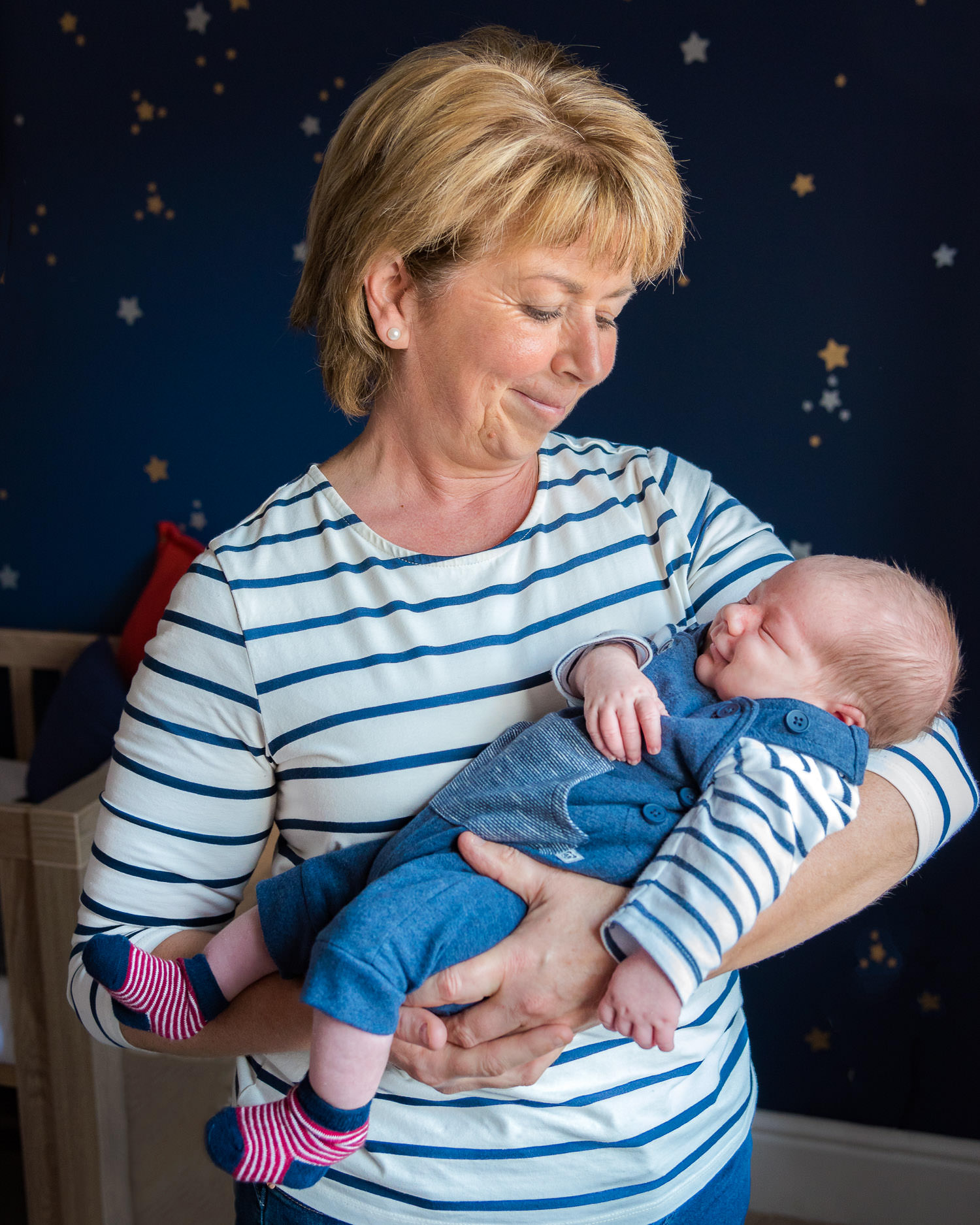 Grandma cuddling baby grandson during maternity shoot
