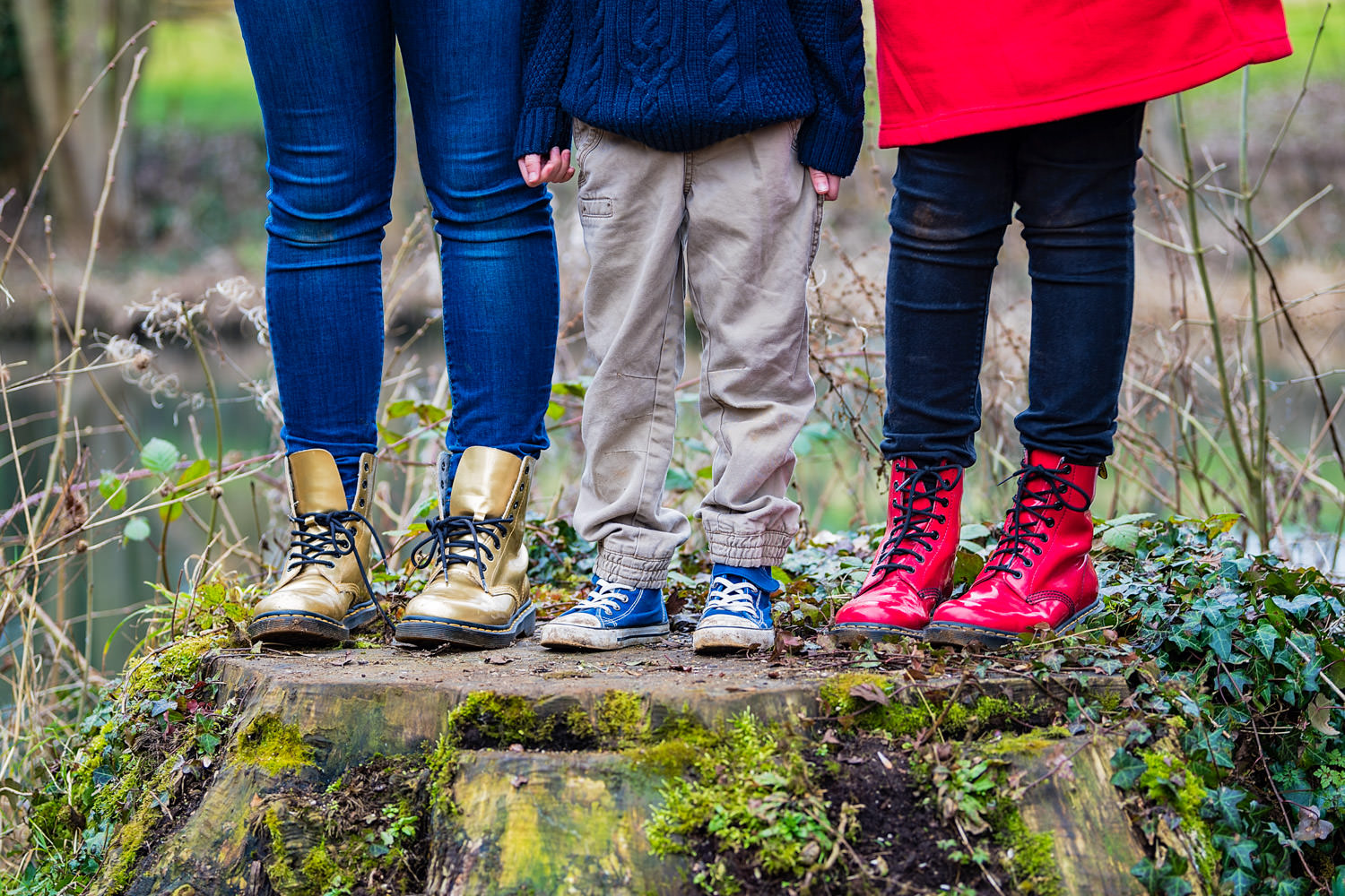 children's legs and shoes standing on tree stump