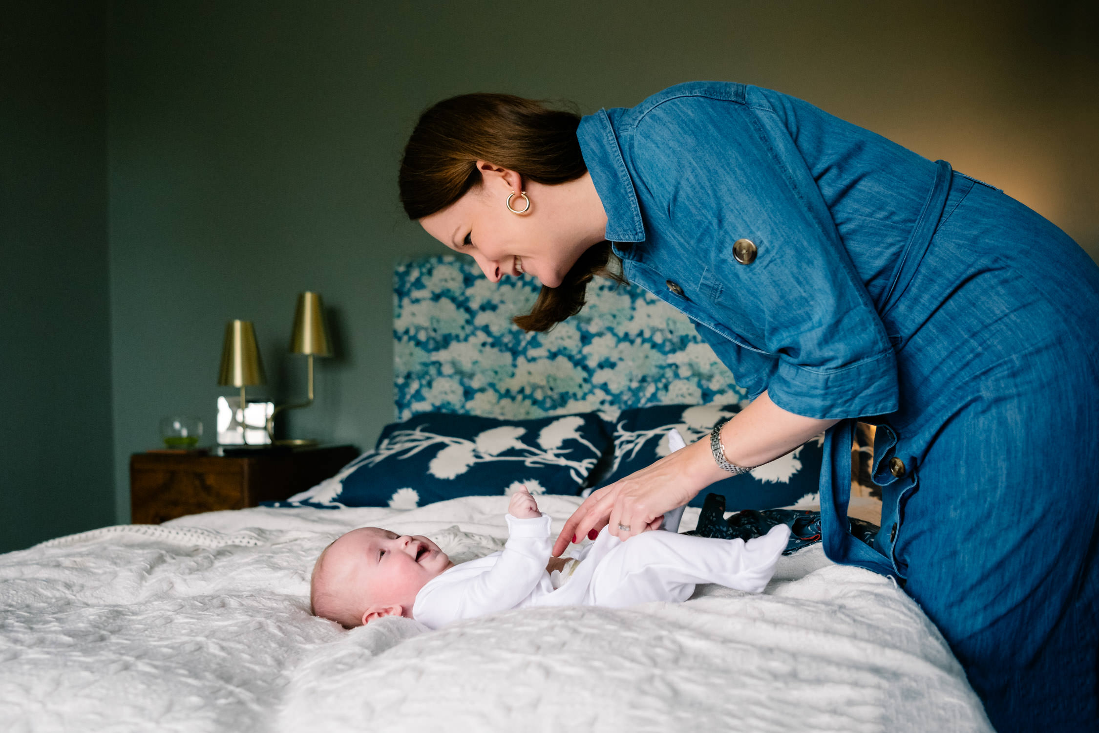Mother leaning over a baby lying on the bed