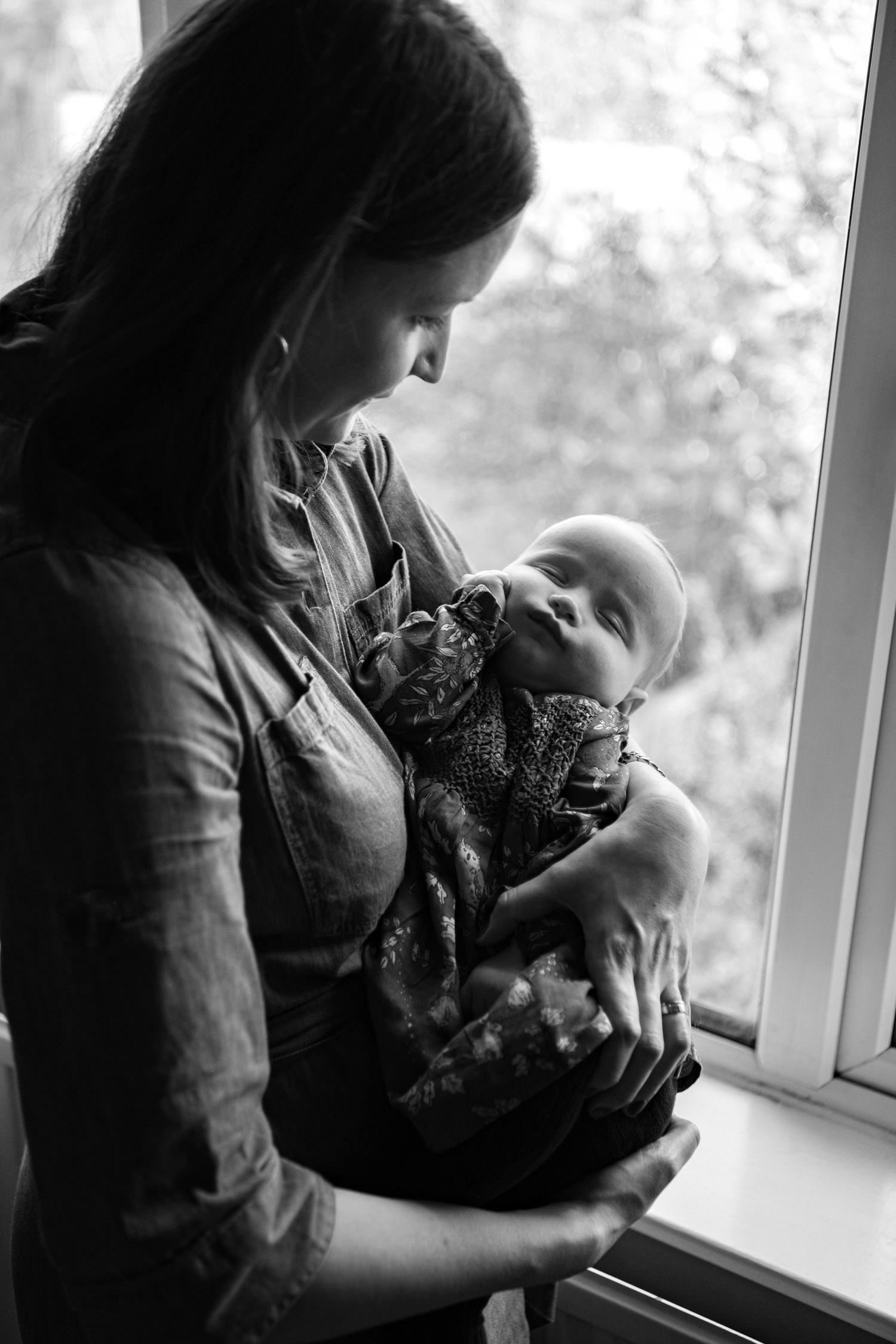 Black and white photo of a mother holding her baby by a window