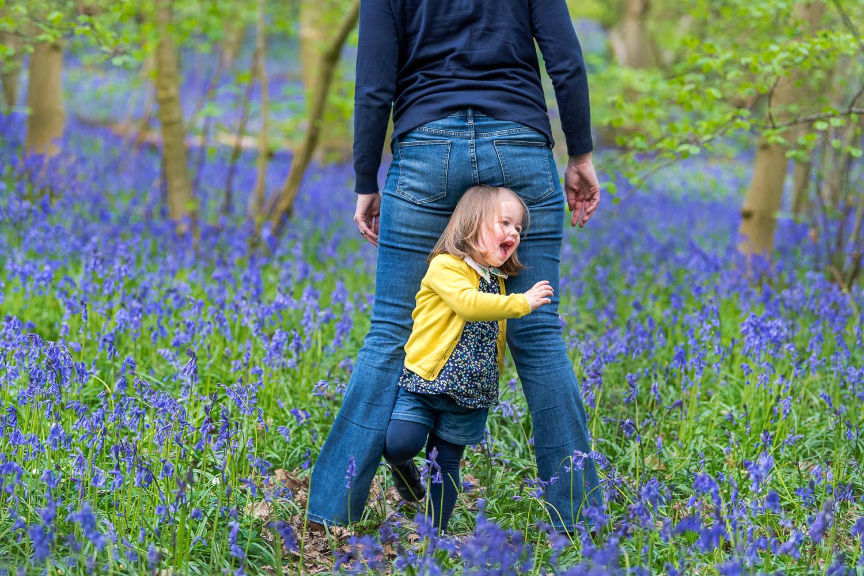 Toddler running through Mum's legs in bluebells