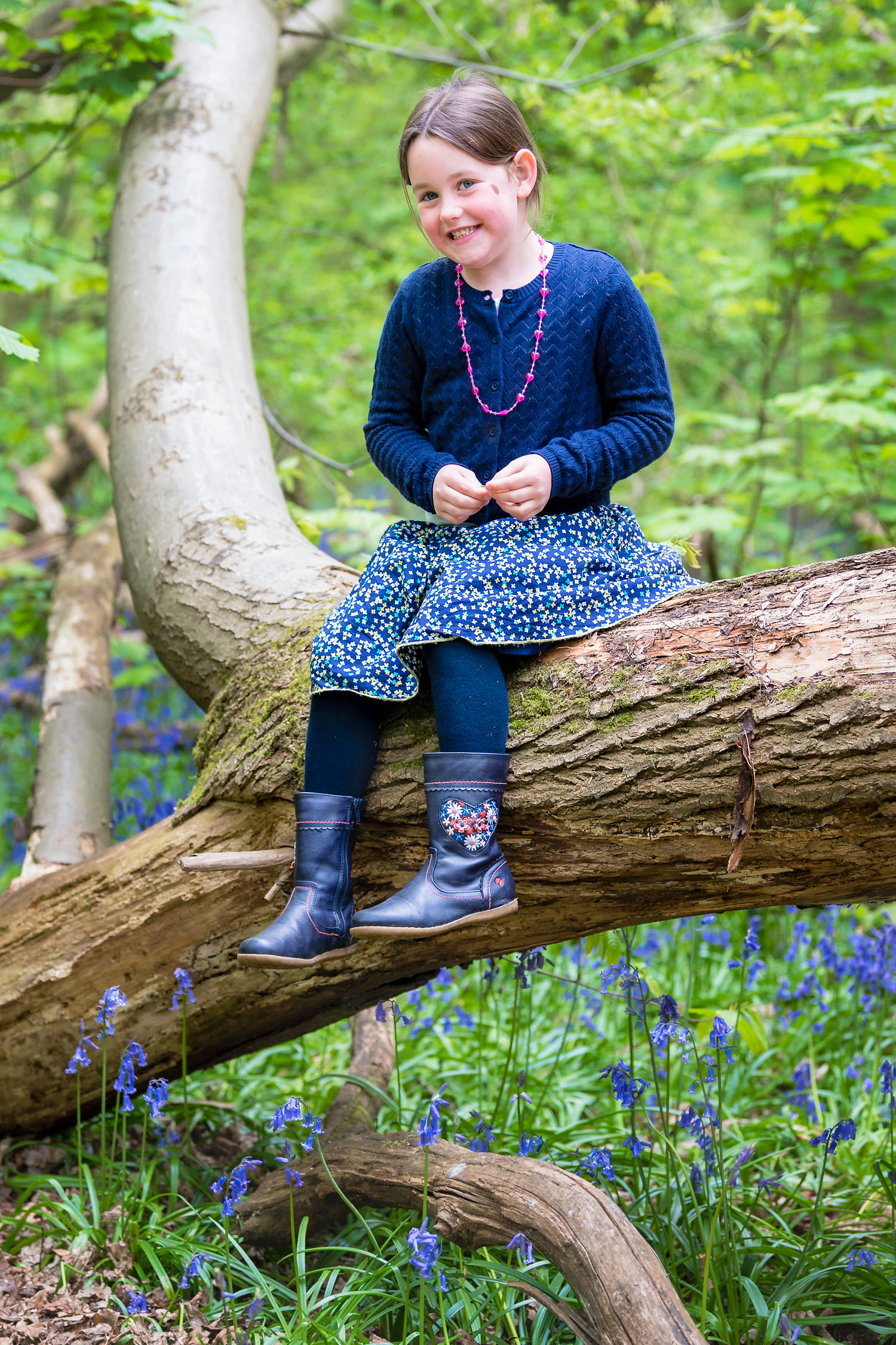 Girl sitting on tree branch during bluebell shoot