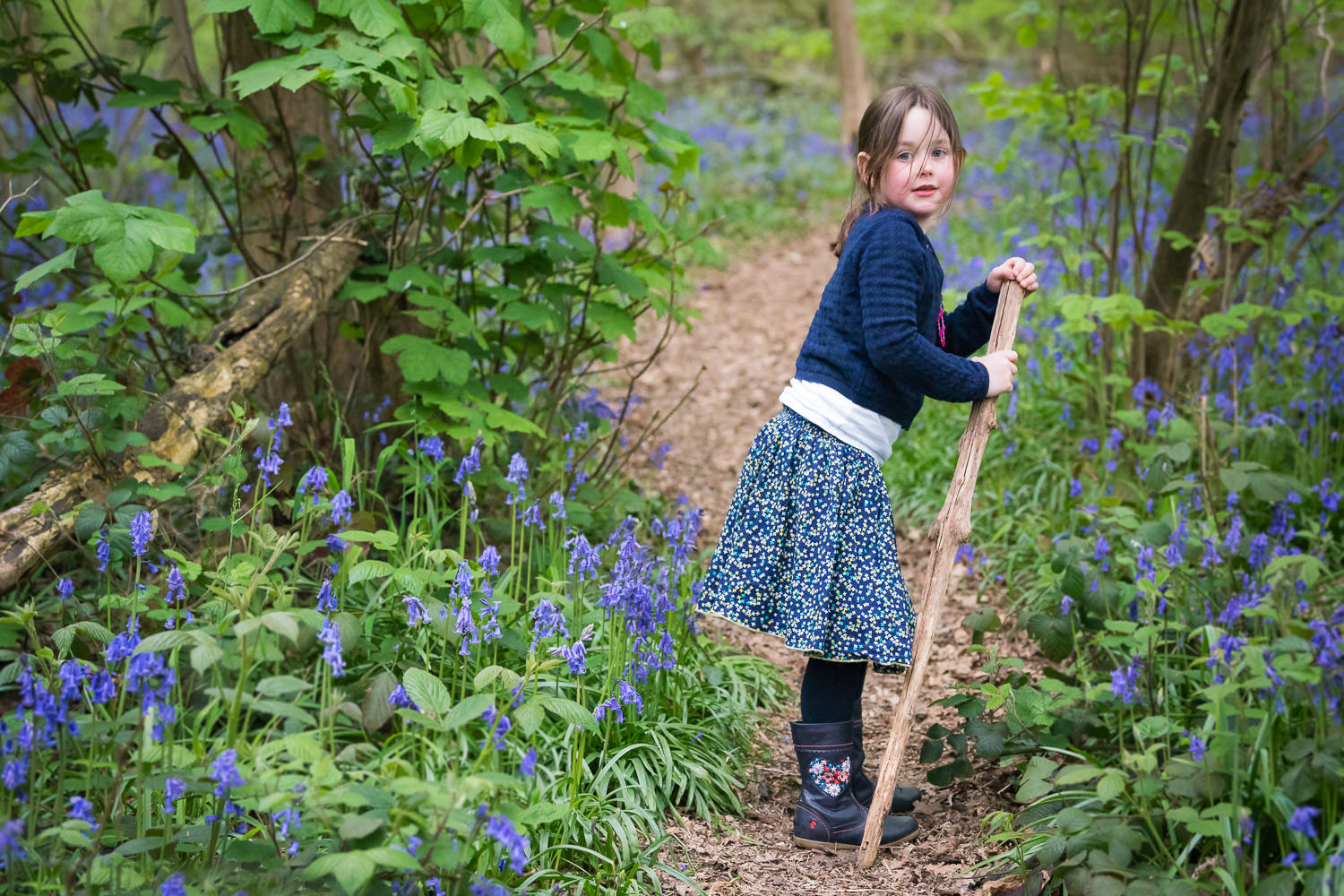 Girl walking along path in bluebells during football shoot