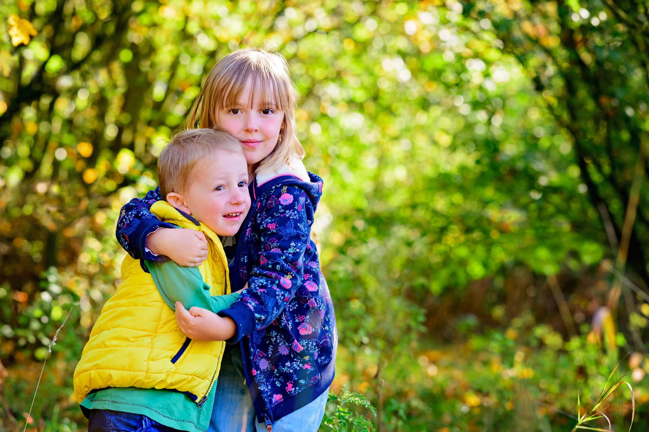 Siblings hugging outdoors