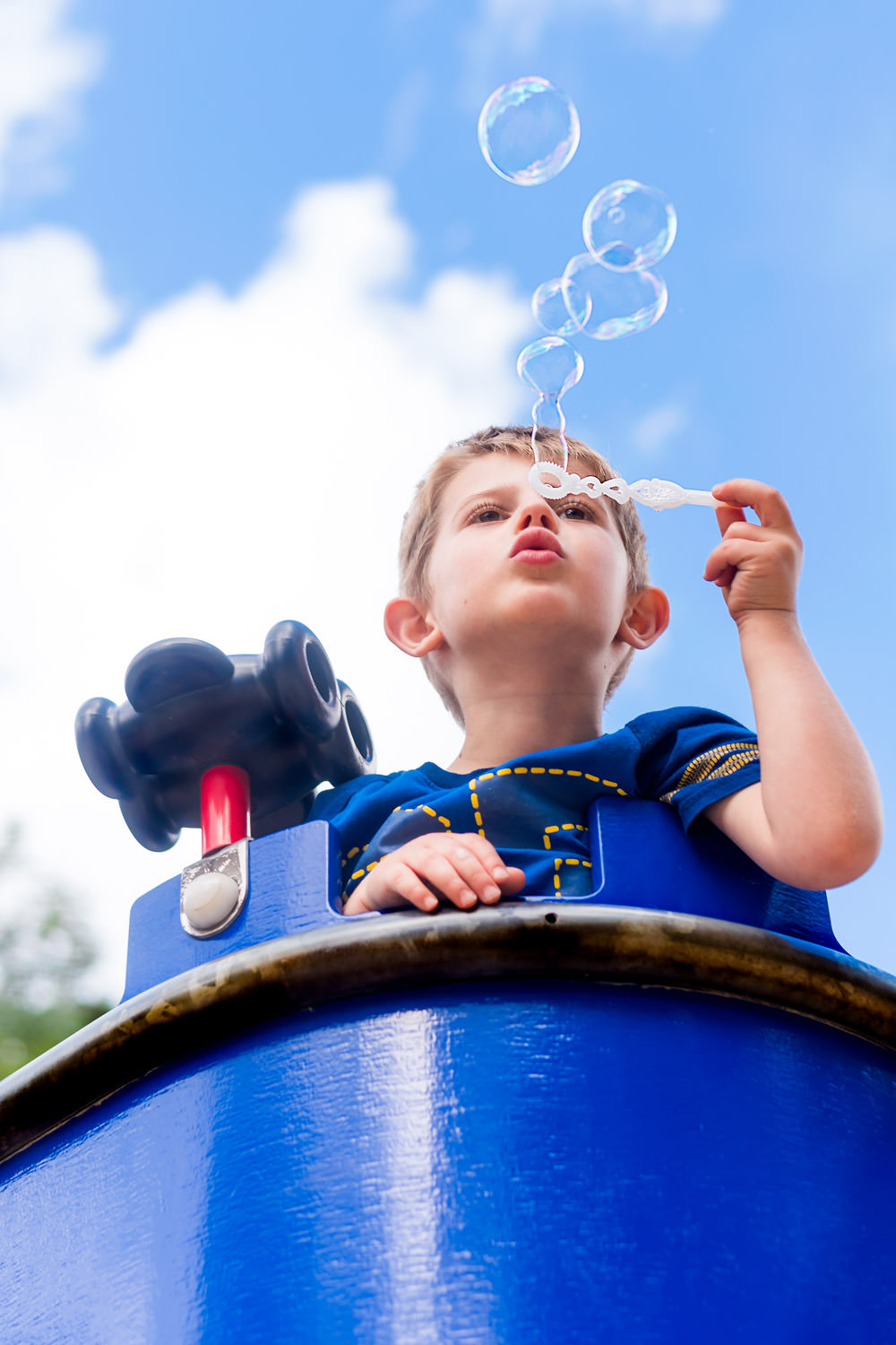 Boy blowing bubbles into blue sky wearing blue t-shirt from blue playground fort