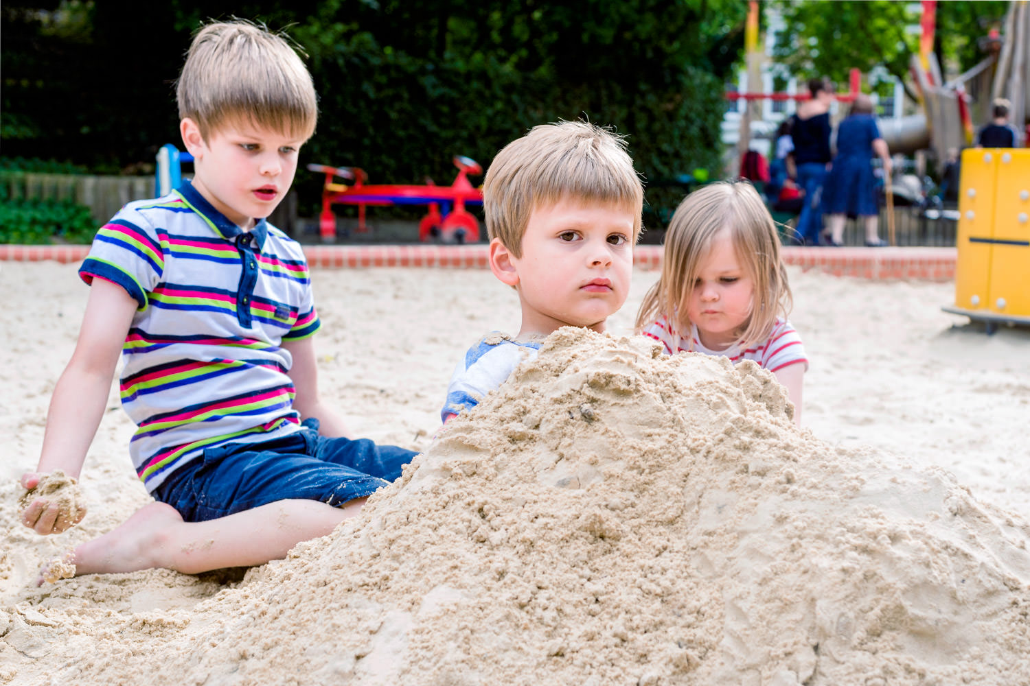 unhappy boy buried in sand by brother and sister