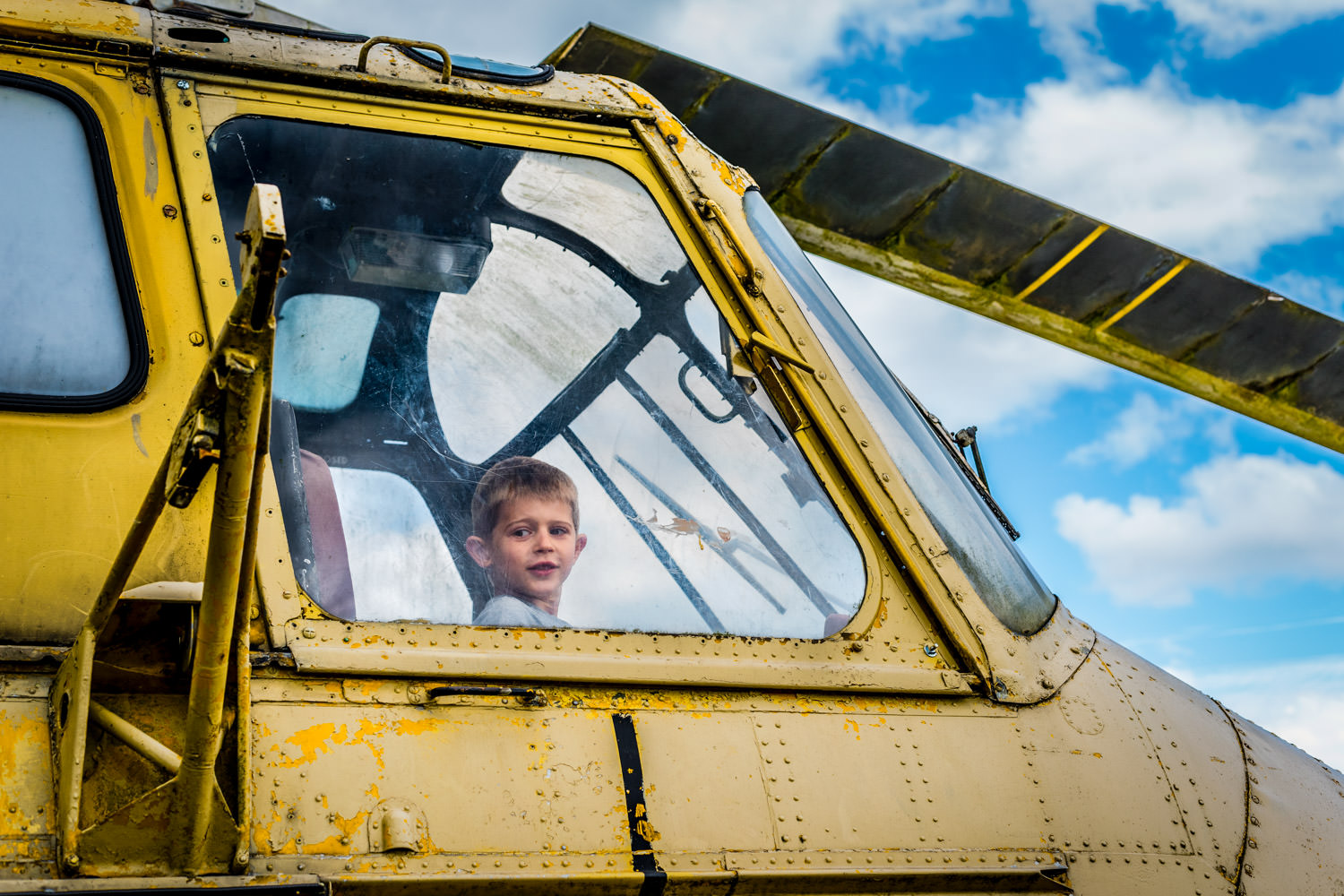 boy sat in pilots seat of yellow helicopter