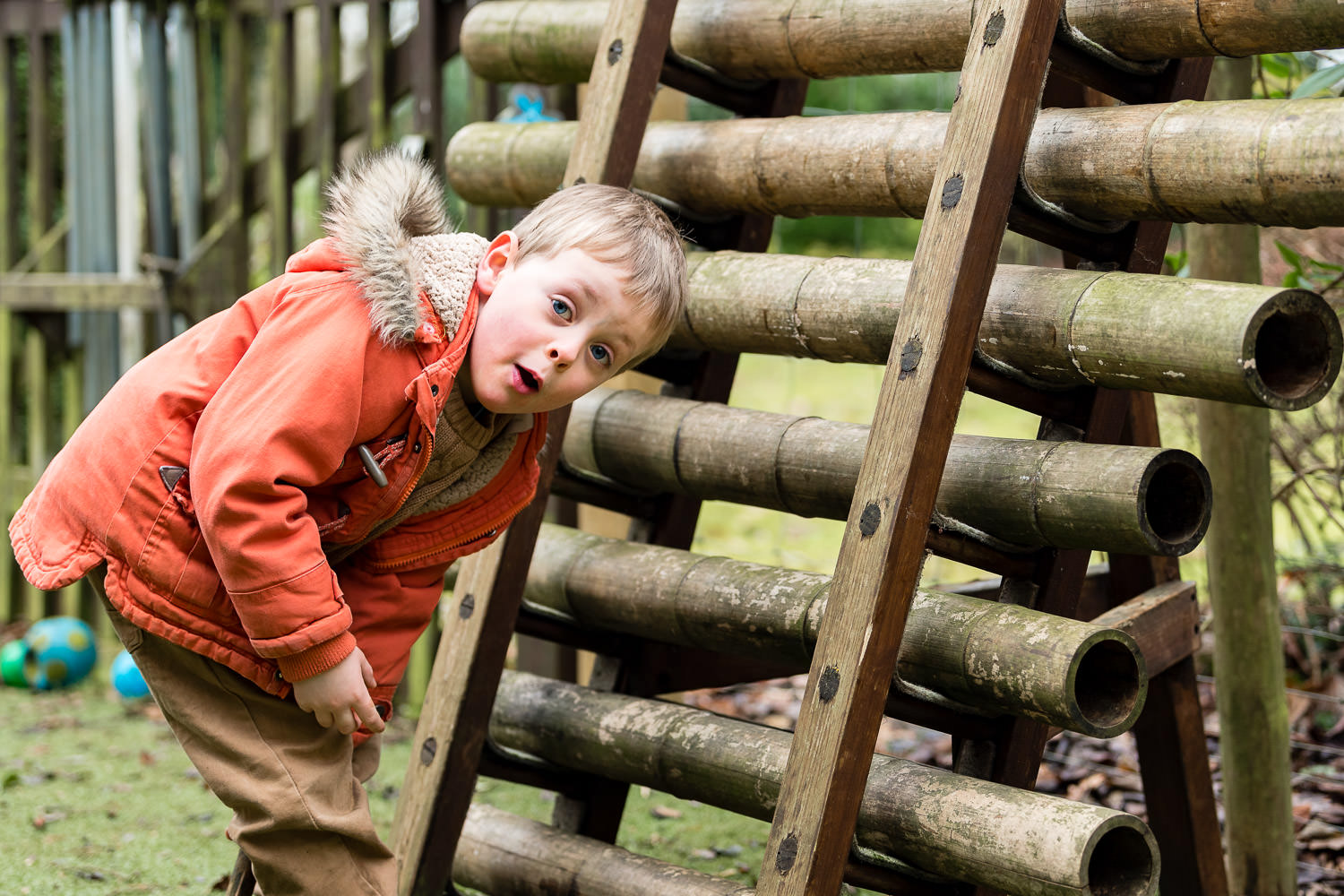 Boy playing on wooden pipes at nursery