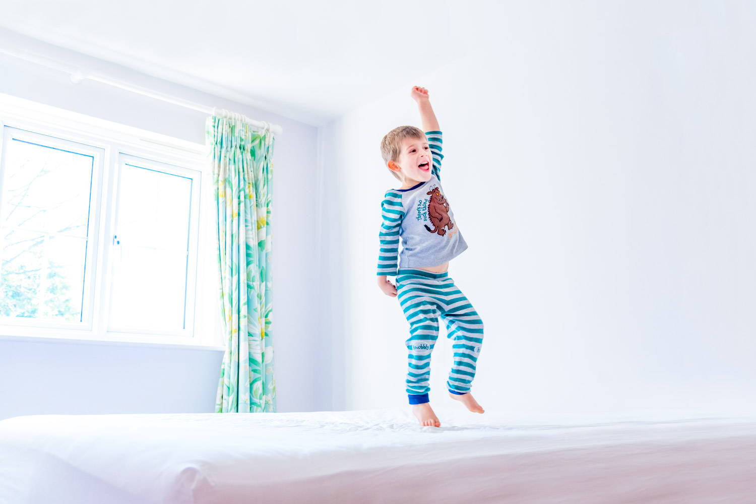 Boy in pyjamas jumping on bed
