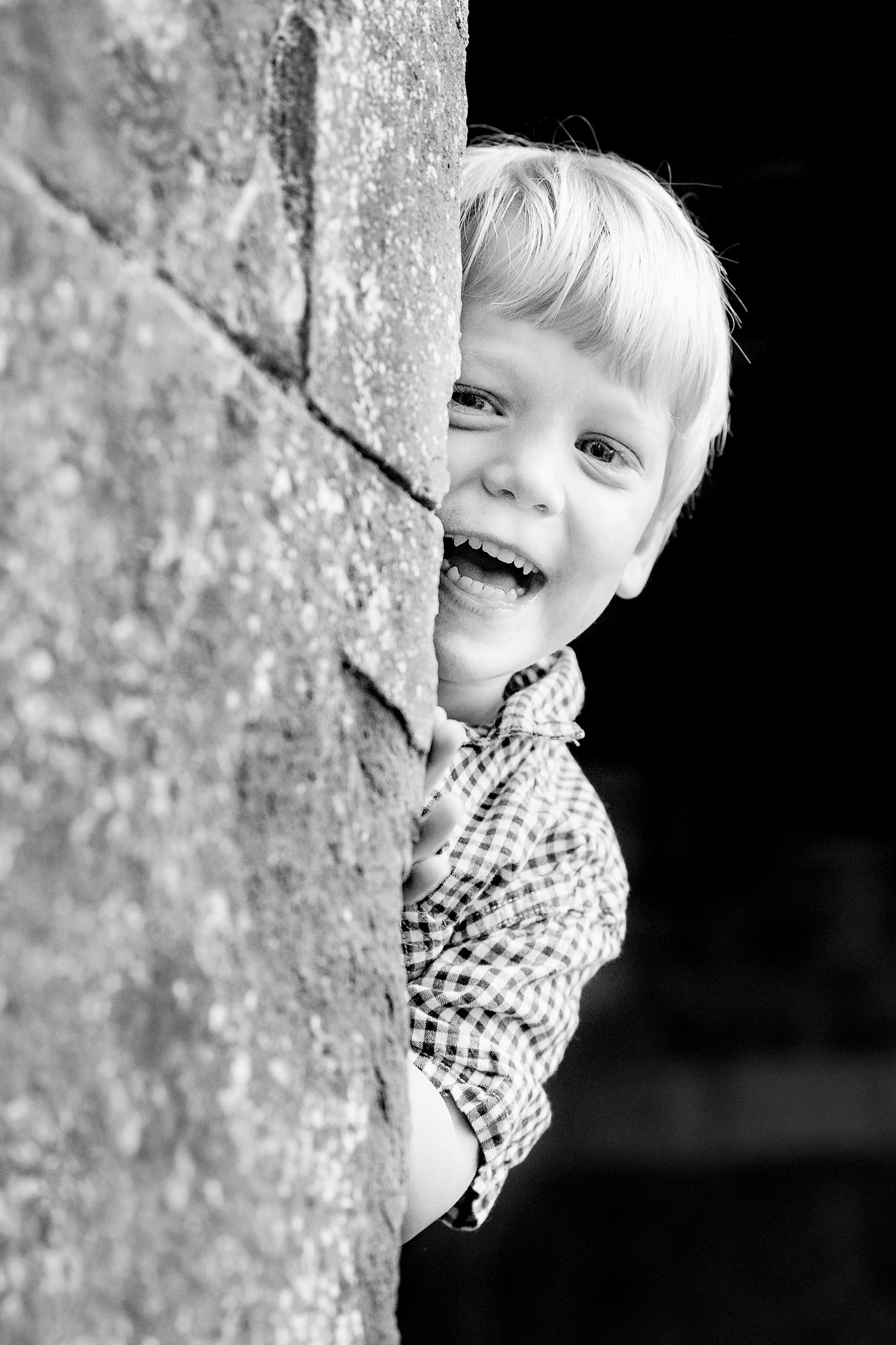 Boy looking around a wall