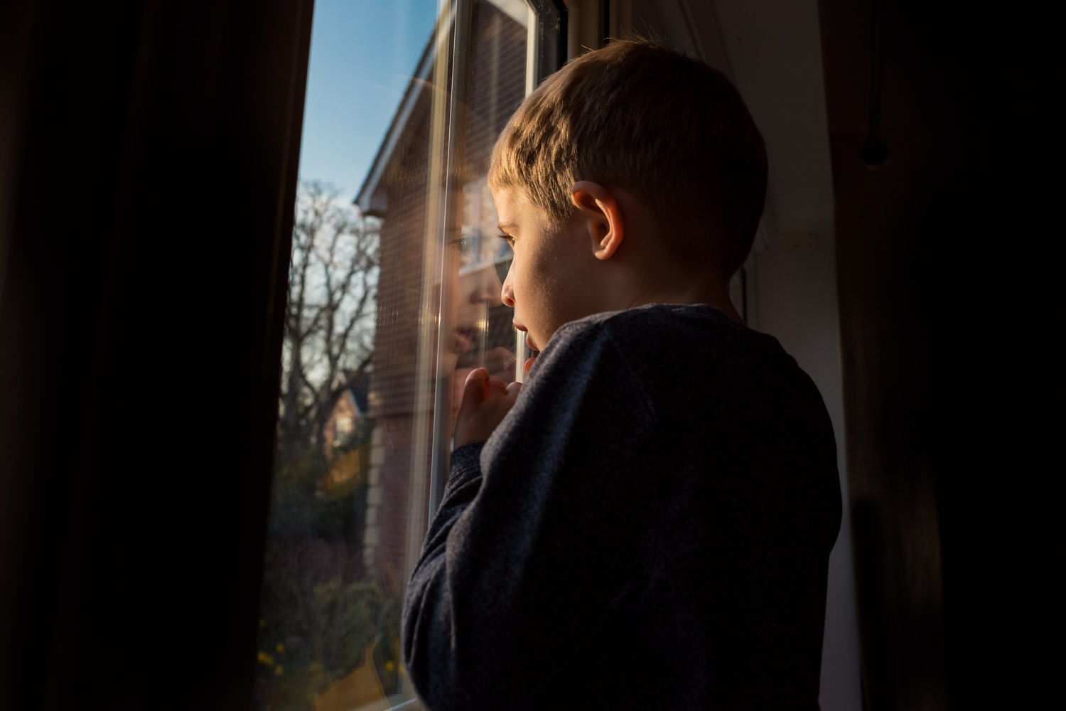 Boy looking out of window with reflection of his face