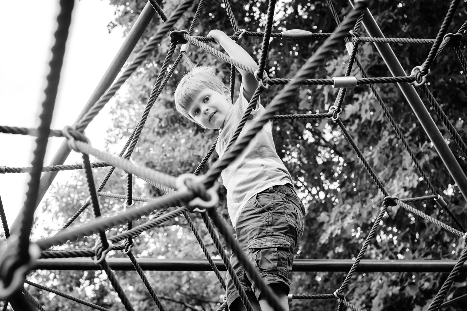 Boy peering through rope climbing frame at camera