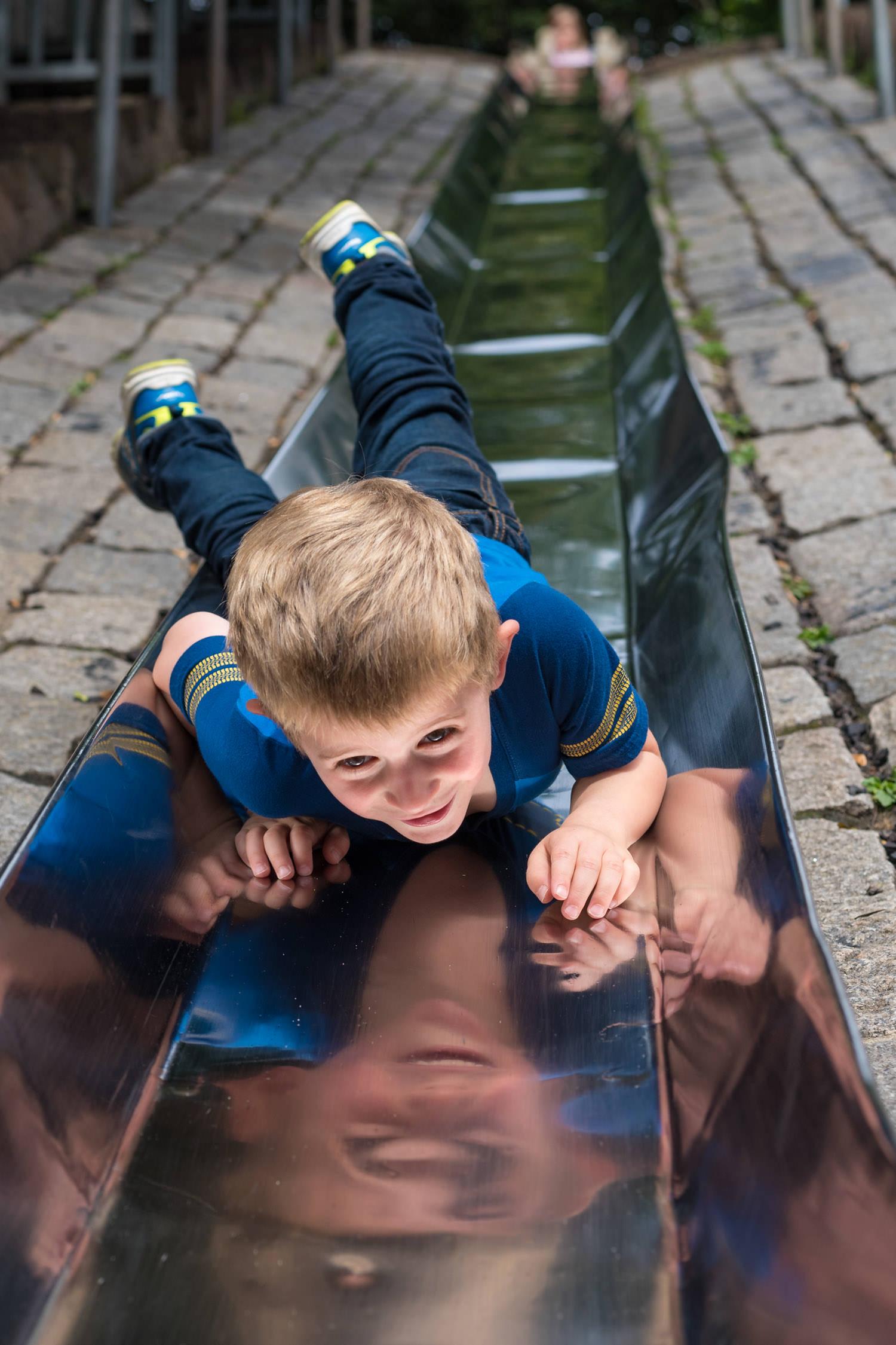 Boy coming down a shiny metal slide head first