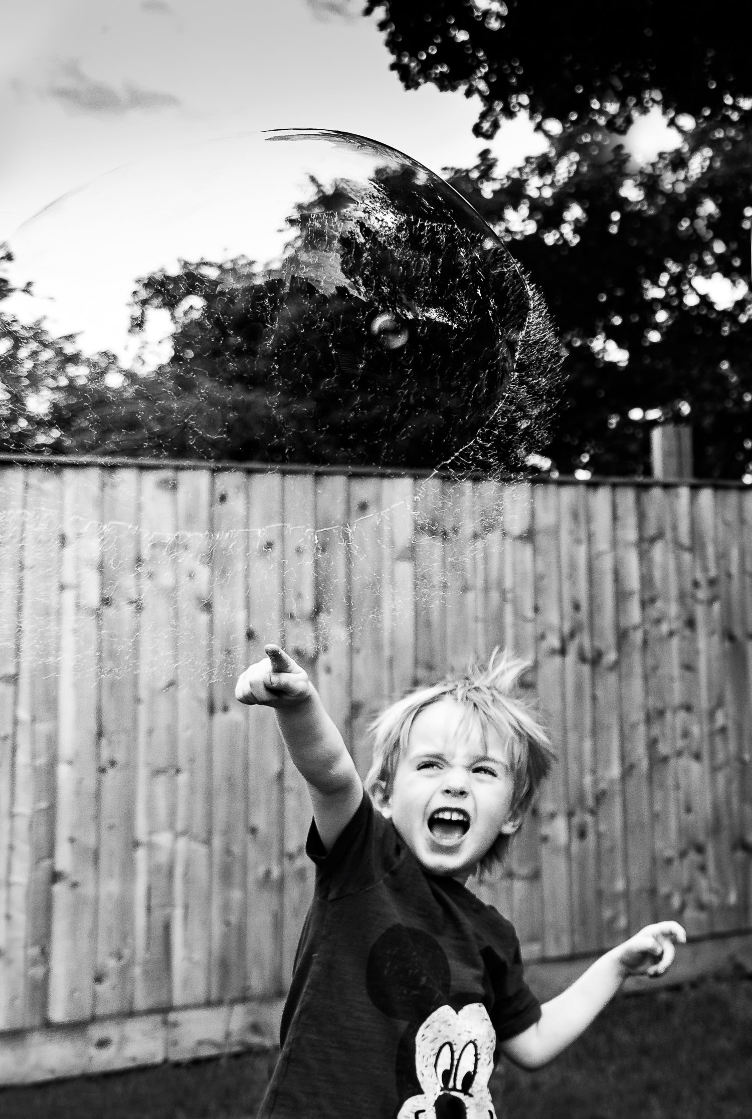 Boy bursting large bubble above his head