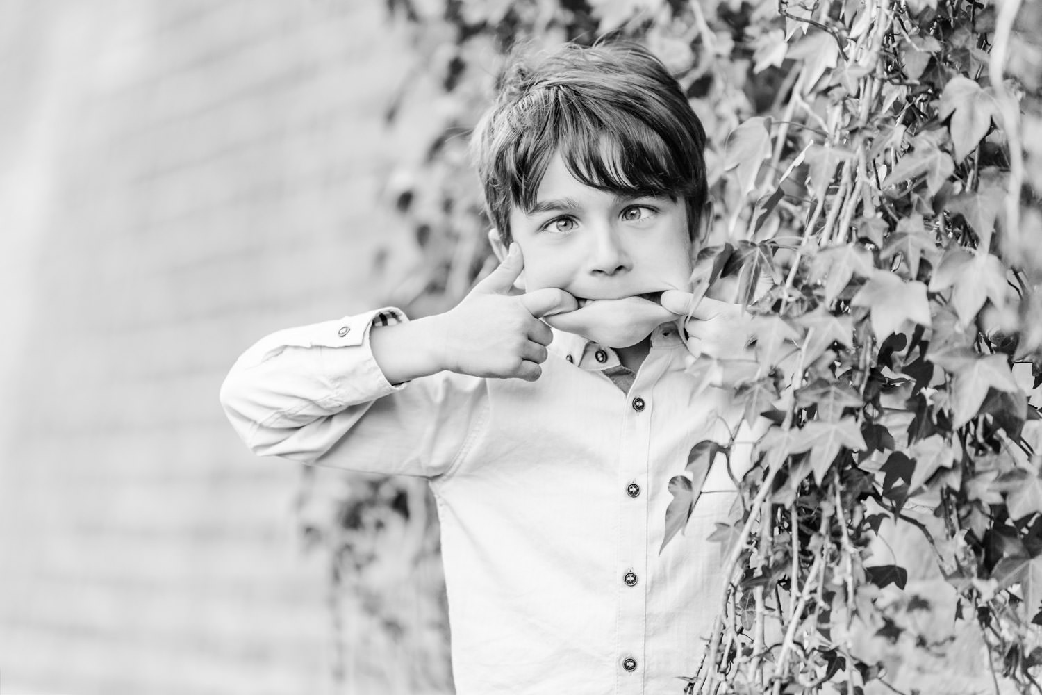 Boy pulling funny face at the camera during family photo shoot
