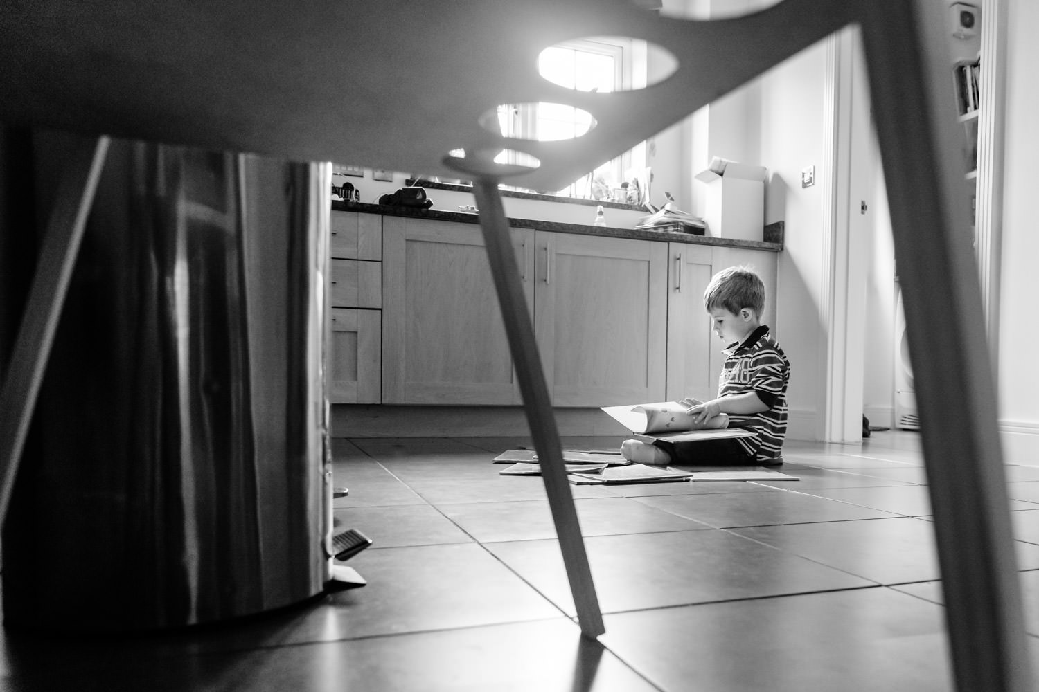 Boy sat on kitchen floor reading books