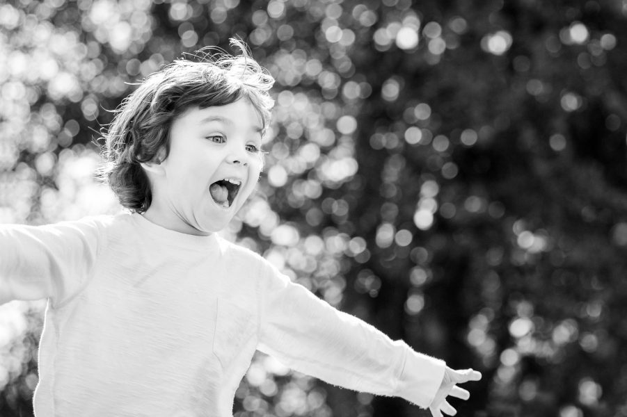 Boy running with arms stretched out wide