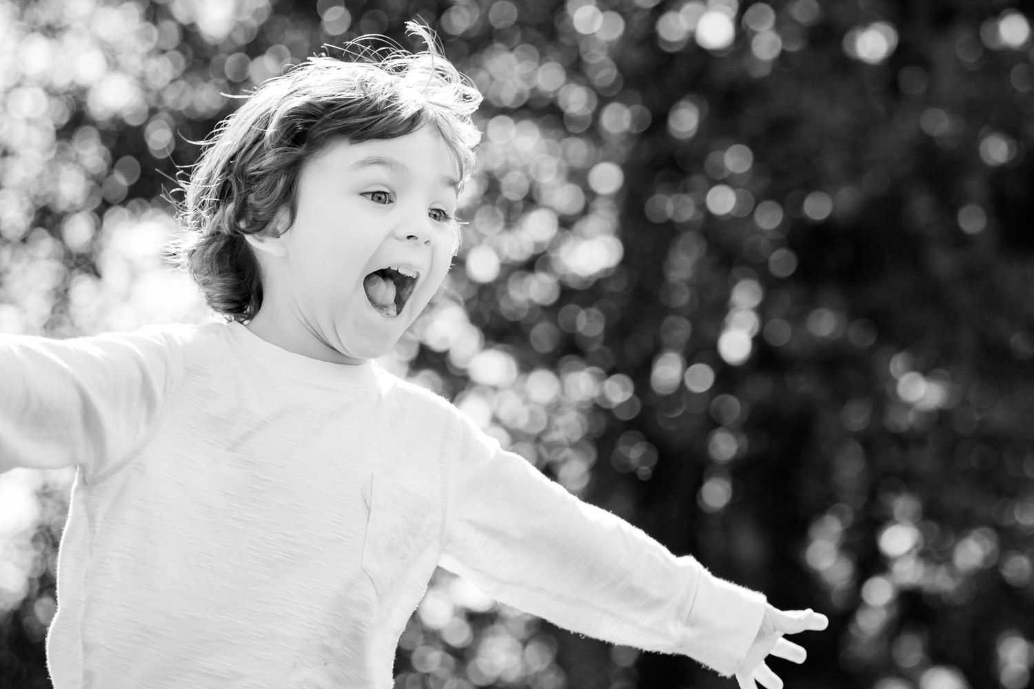 Boy running with arms outstretched during family photo shoot