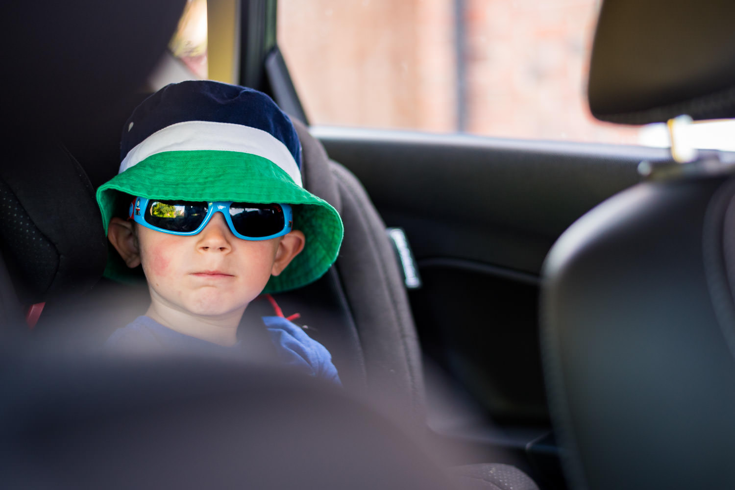 boy sat in car with sunglasses and hat