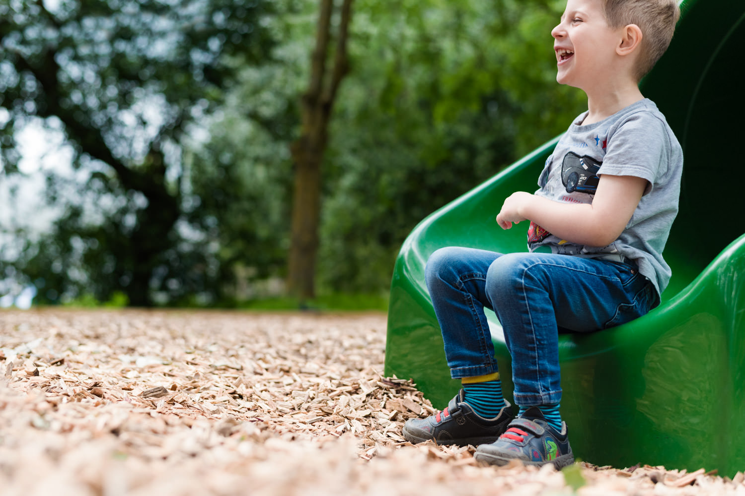 boy sat on foot of slide laughing