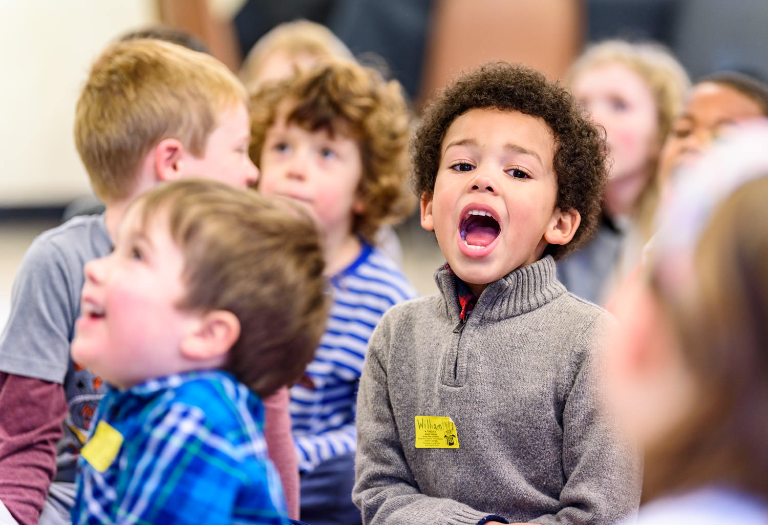 Boy shouting in a crowd of children sitting down