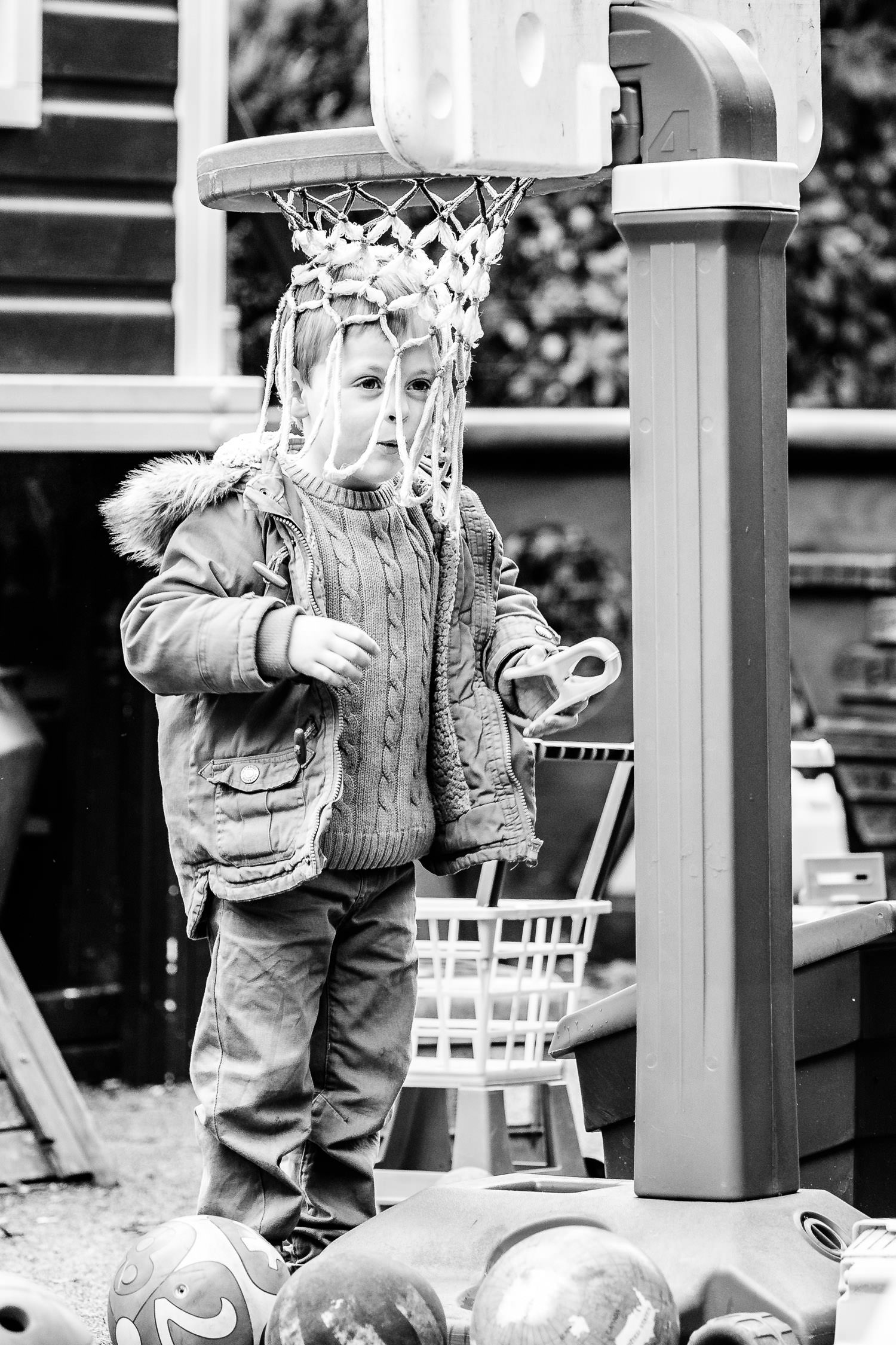 Boy with head in basket ball hoop at nursery