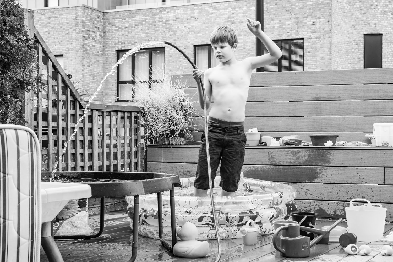 Boy stood on roof terrace pouring water out of hose
