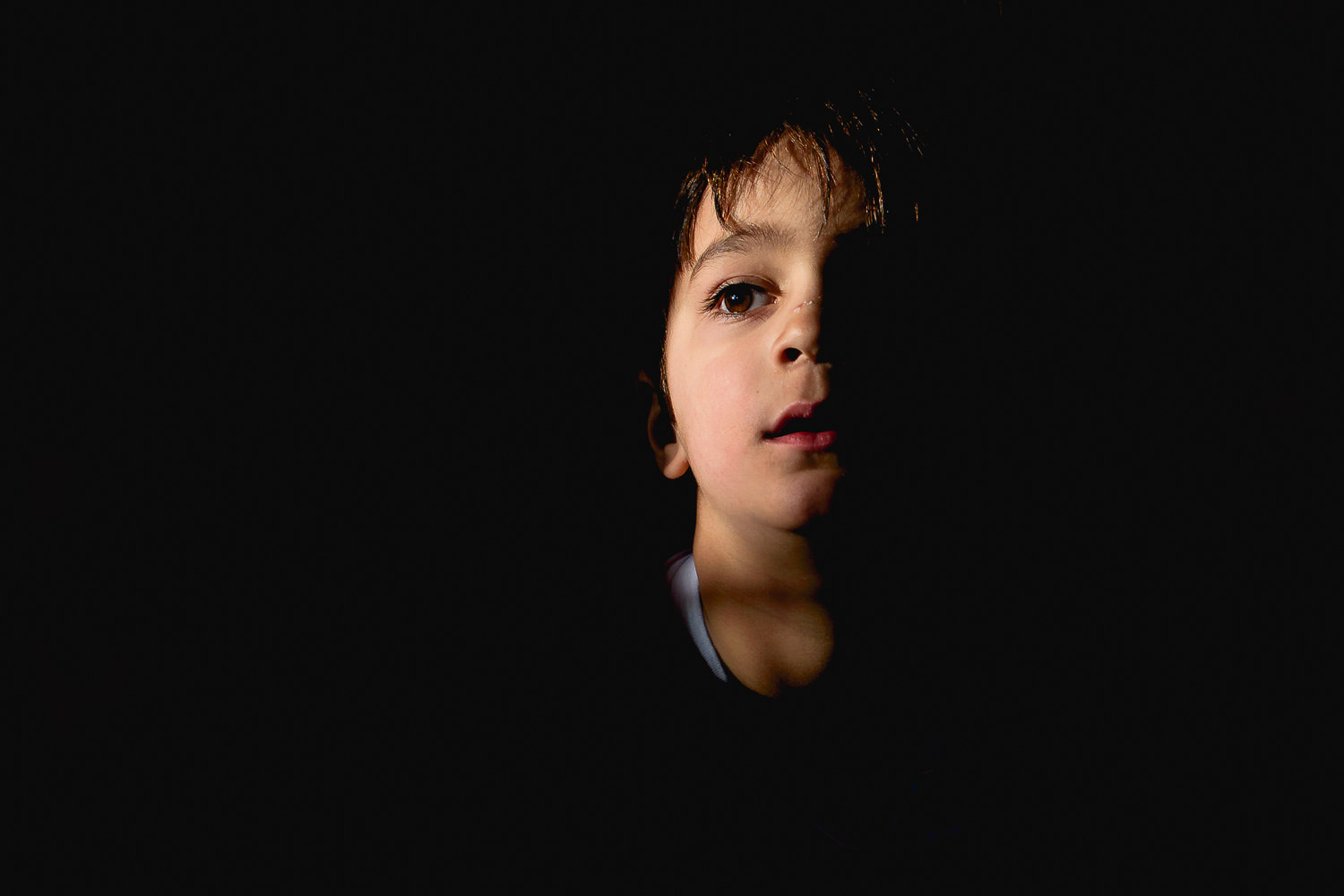 Boy sat in darkness with half his face in patch of light