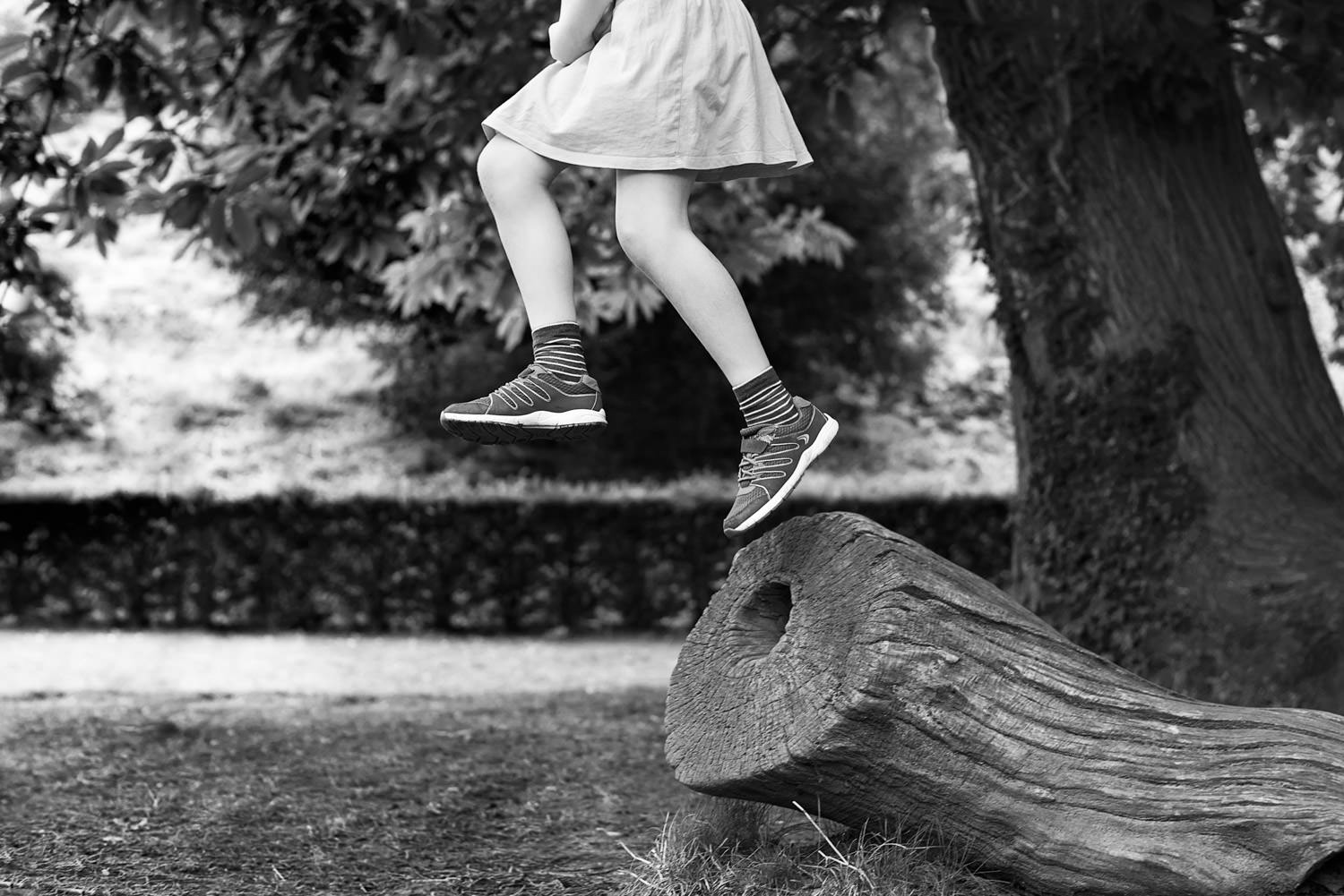 Girl suspended mid air as she jumps off log