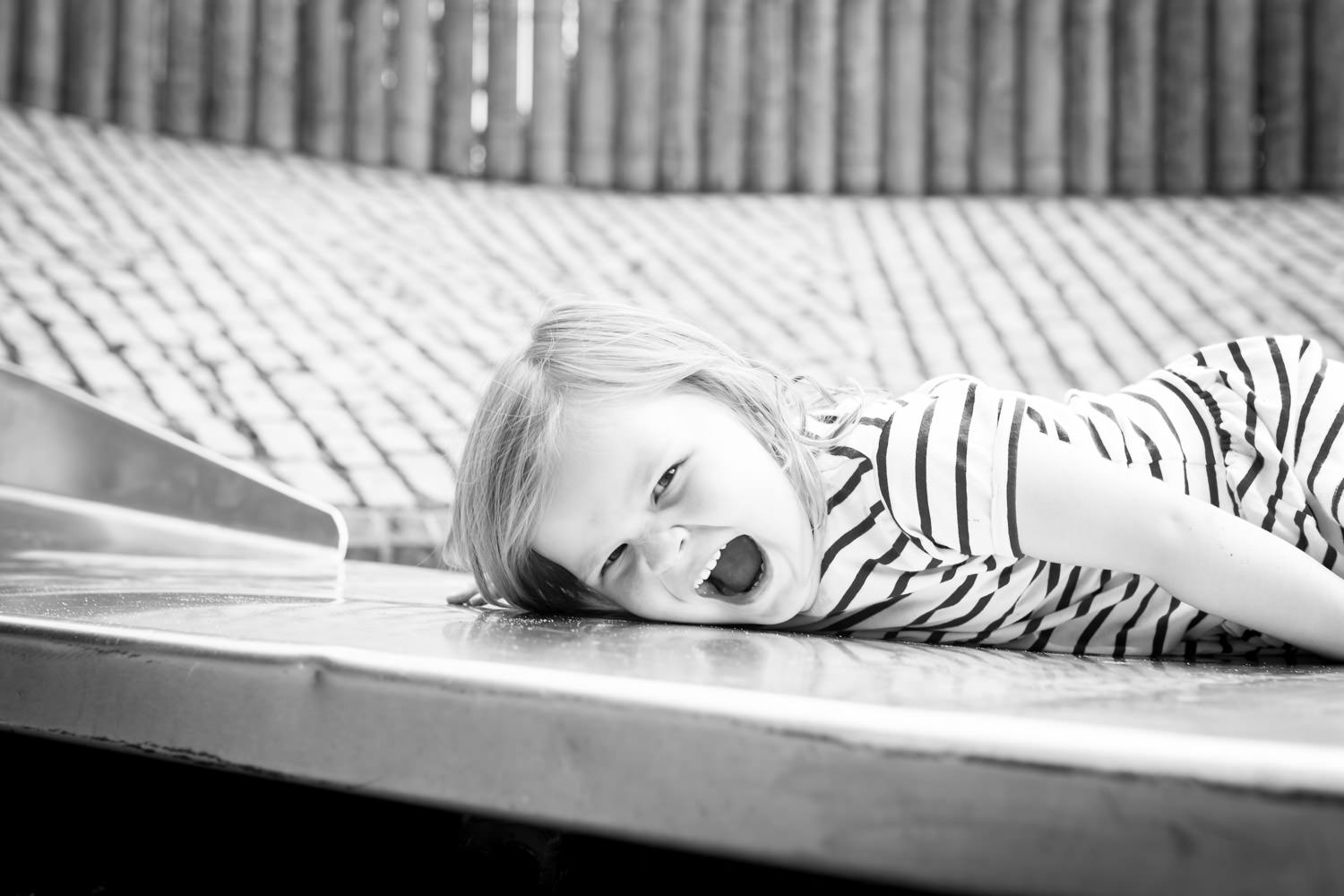 girl lying on bottom of the slide laughing