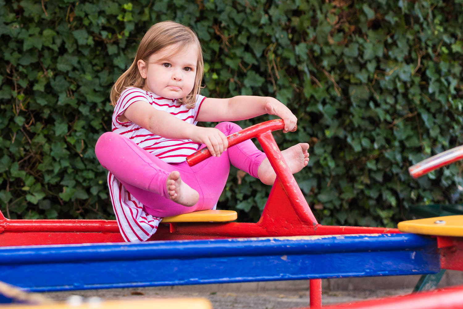 girl sat on colourful roundabout in playground