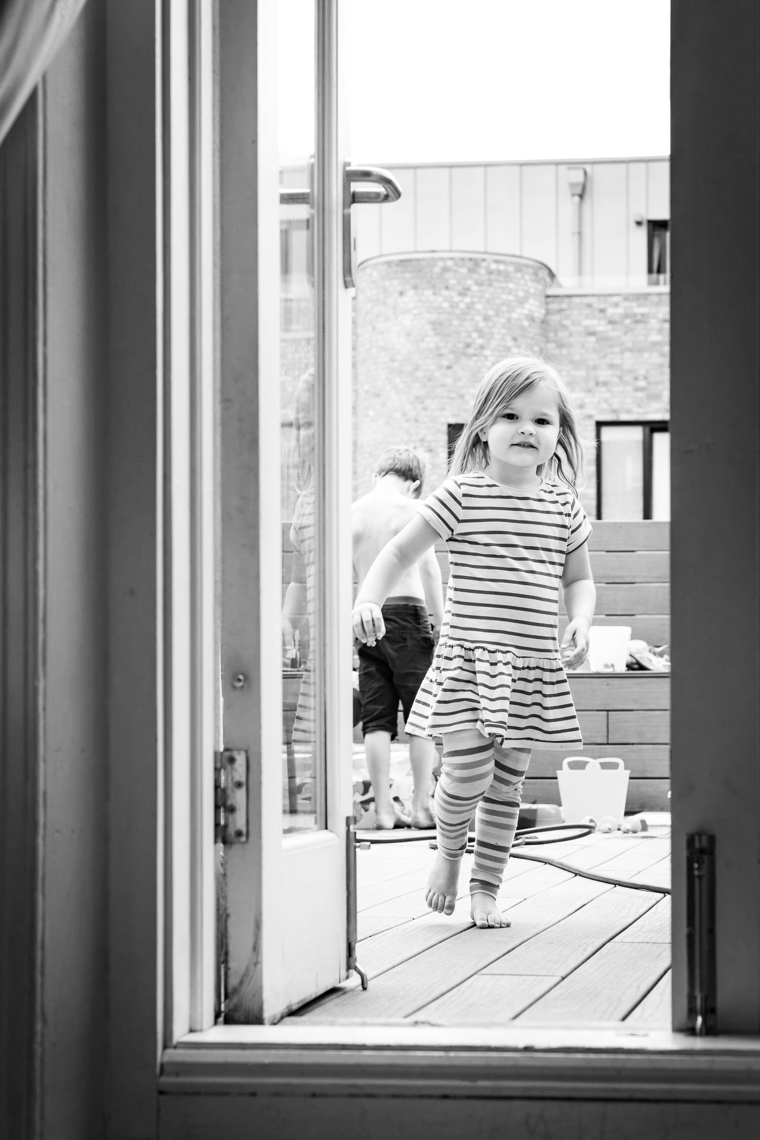 Girl in striped dress running inside from roof terrace