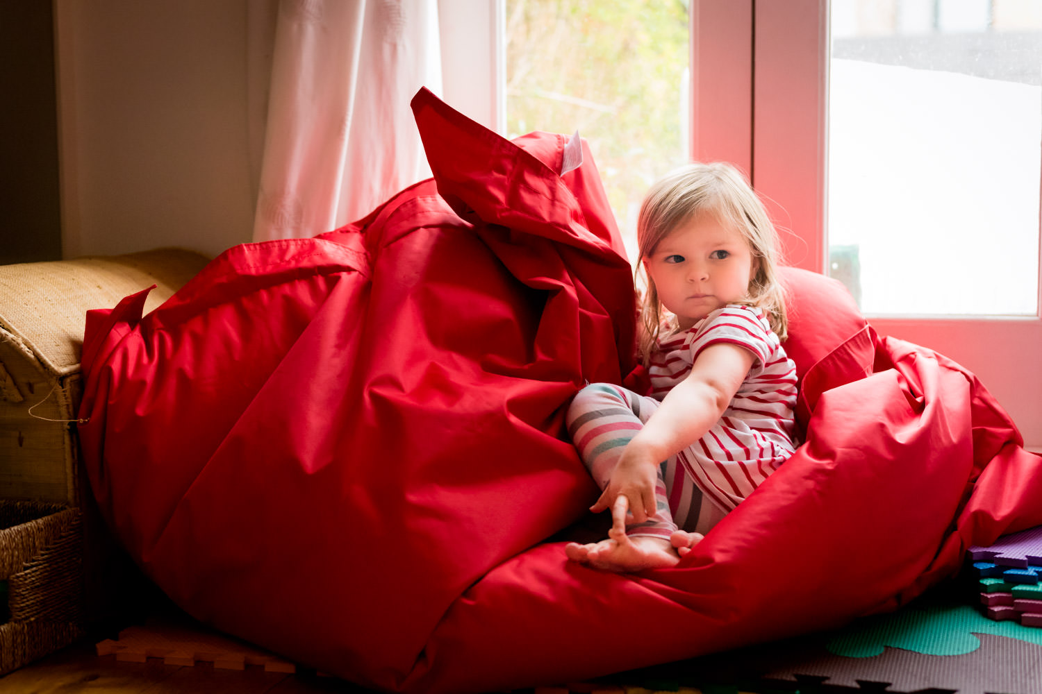 Girl sat on extra large red bean bag