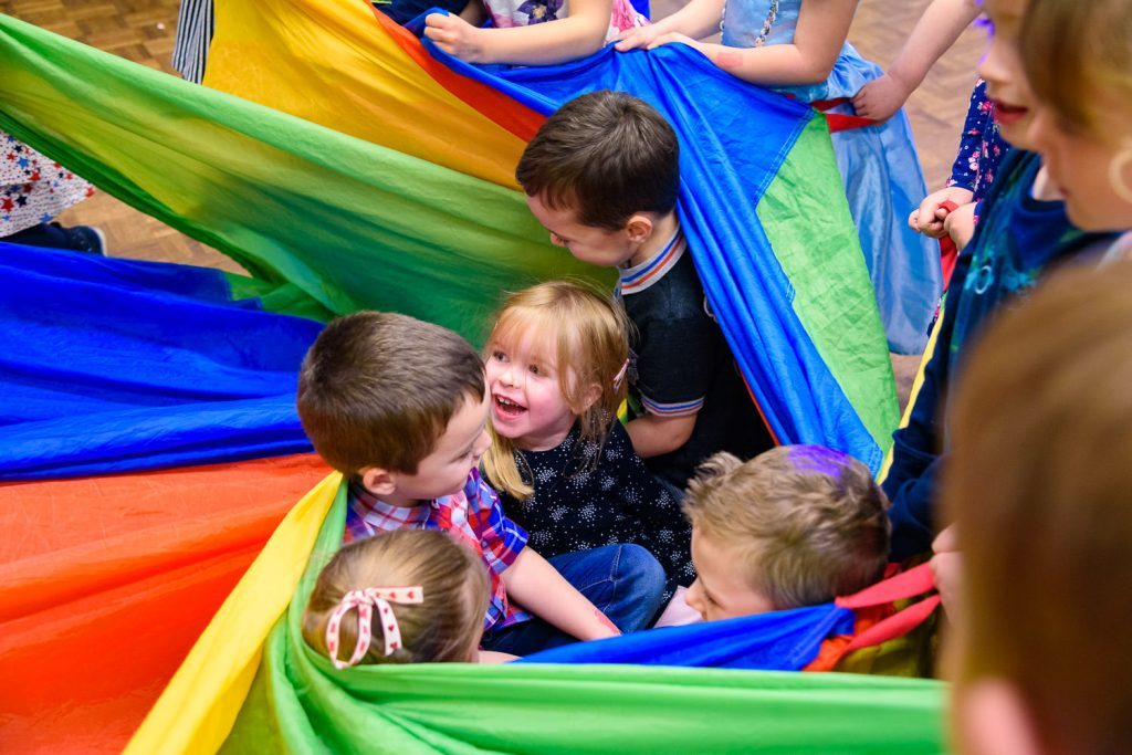 children wrapped up in colourful parachute
