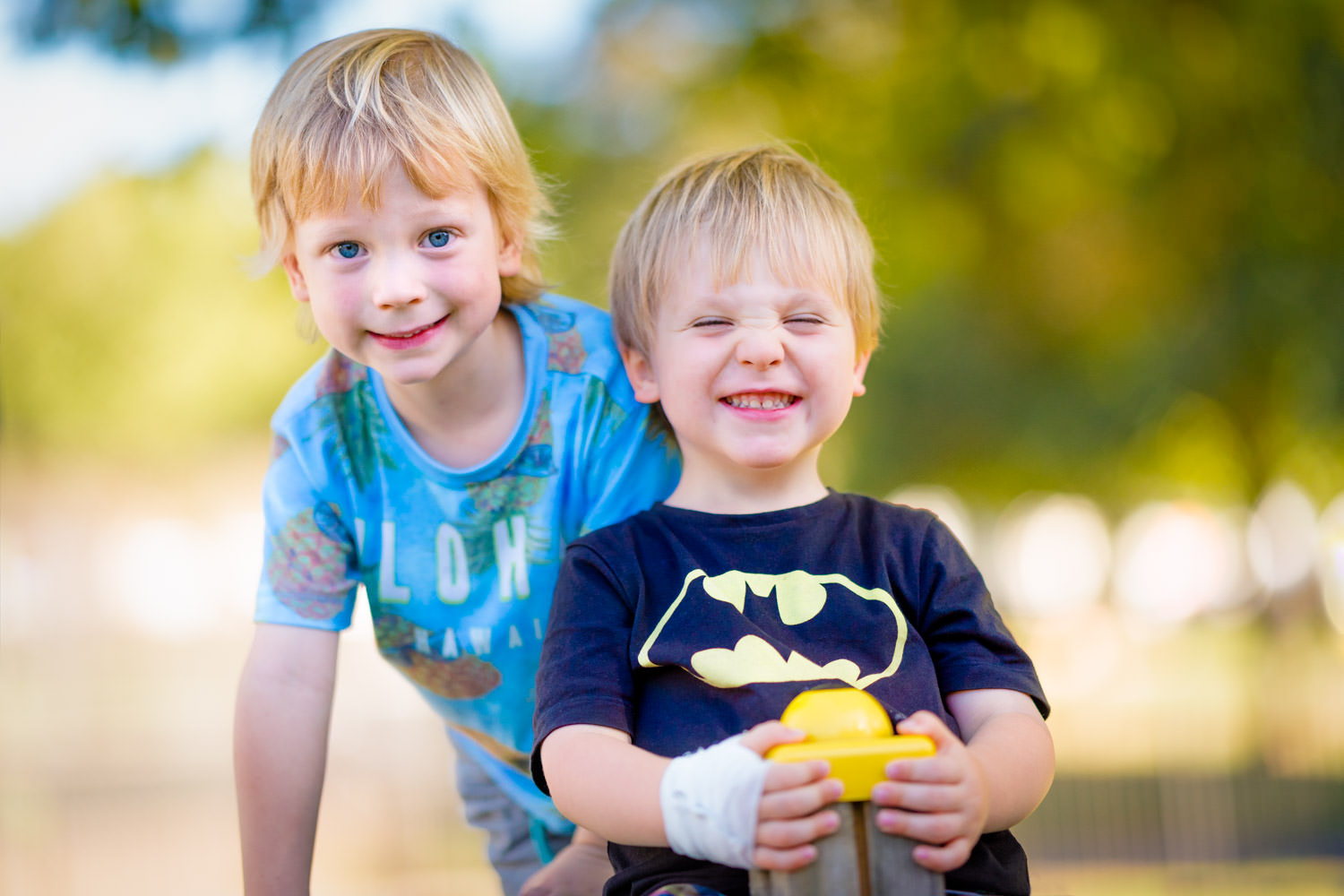 Two blonde boys smiling at the camera with cheesy smile