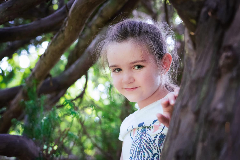 portrait of girl hiding in a tree