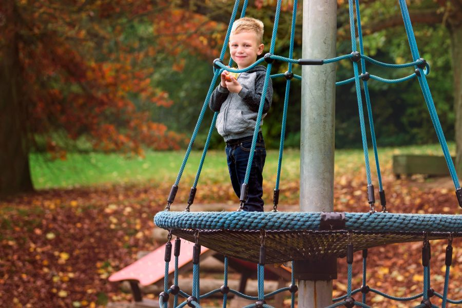 Boy eating apple on climbing frame