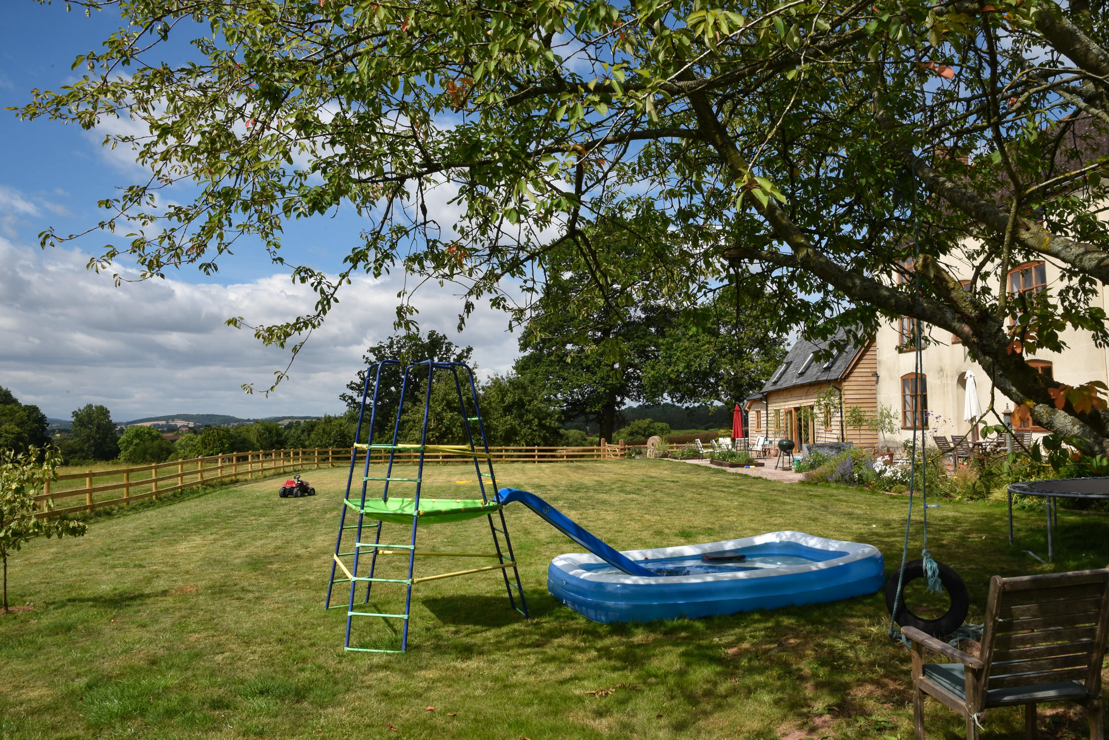 Holiday home garden with climbing frame and paddling pool