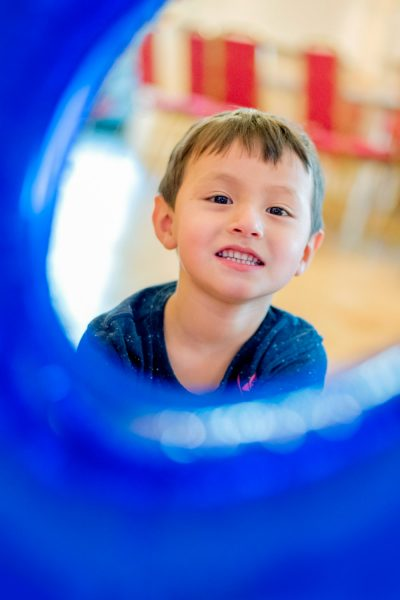 Boy smiling as he looks through the curve of a number 5 shaped blue ballloon