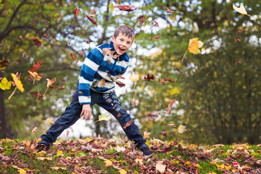 Boy throwing autumnal leaves