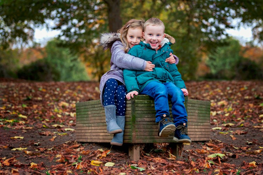 girl and boy hugging on bench surrounded by autumn leaves