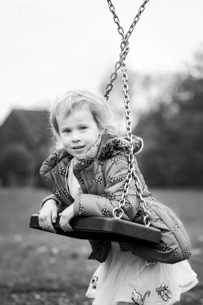 Girl leaning over twisted swing