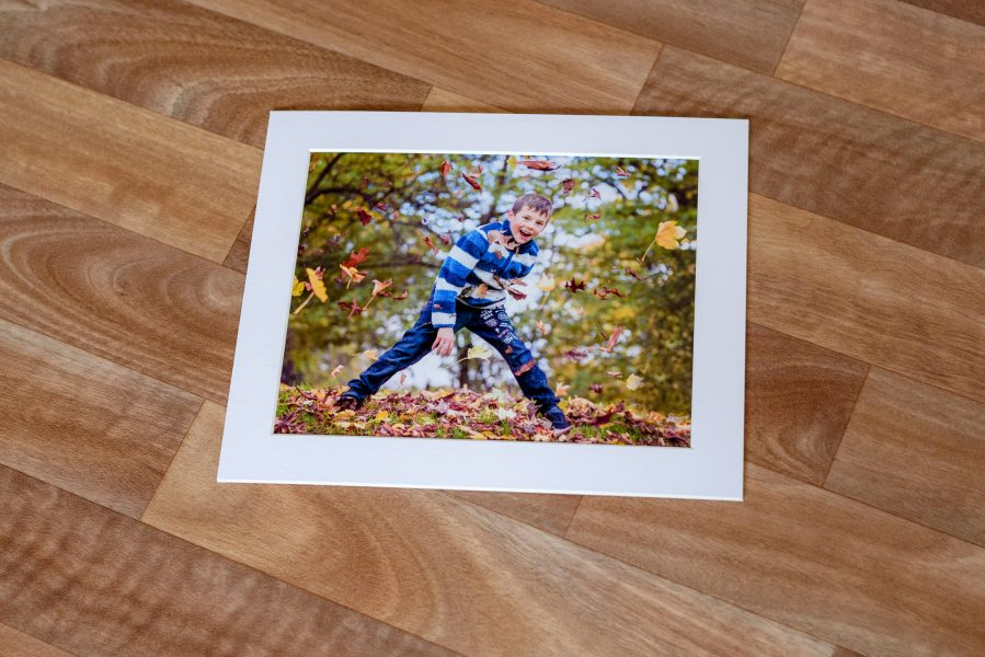 Photo of boy throwing leaves in mount