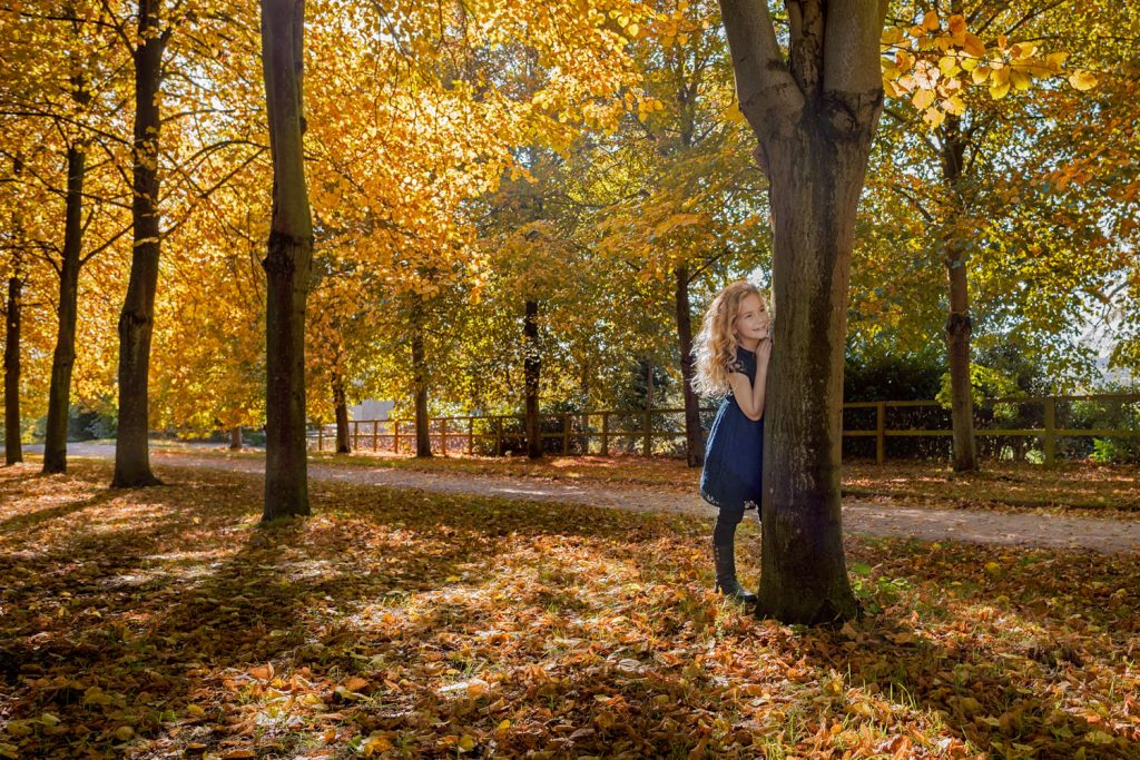 Autumnal eye-catching photos of girl hiding behind trees