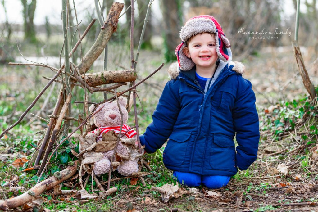 Boy kneeling next to a den he's made out of sticks for teddy bear