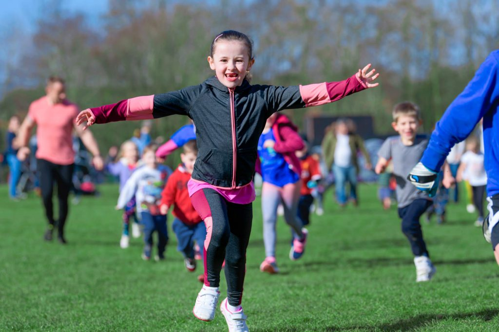 Girl running in race with arms stretched out wide