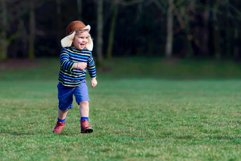 Boy running in stripy top, blue shorts and dear hunter hat