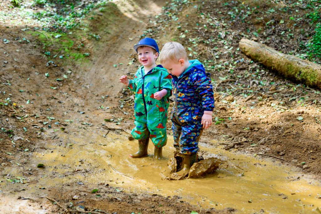 Family Photographer captures boys jumping in muddy puddle