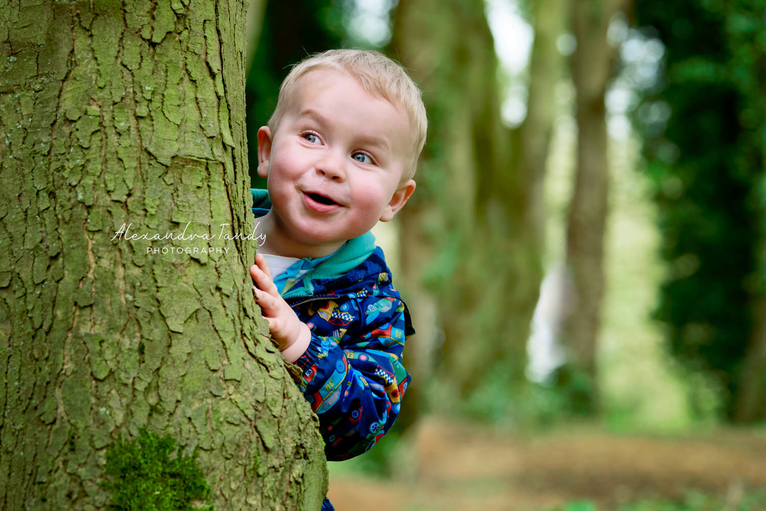 Boy playing peekaboo with family photographer